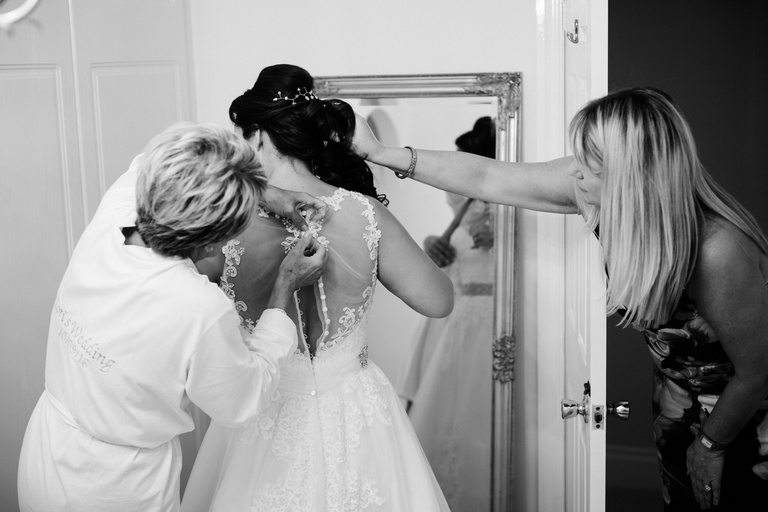 bride being helped into her dress by her mum