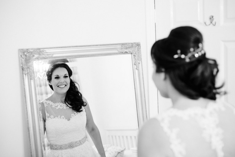 bride admires herself and her dress in the mirror