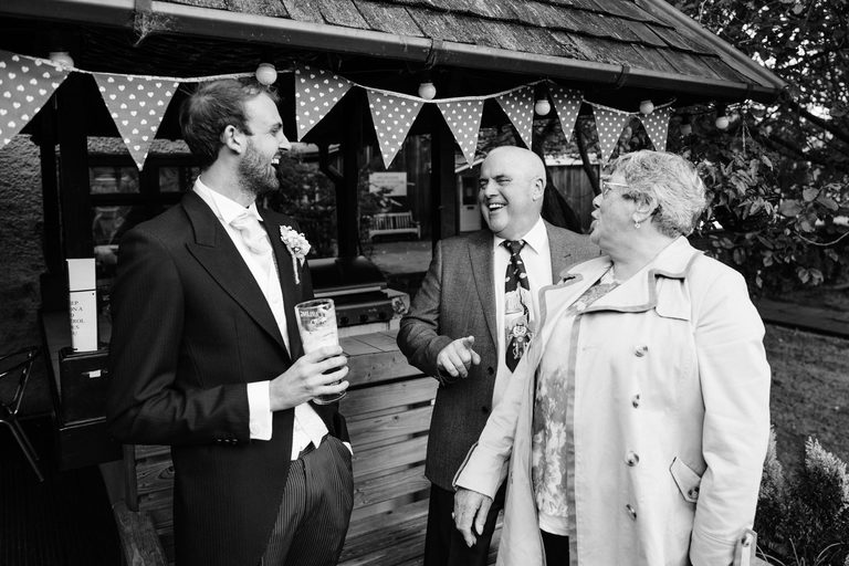Groom laughing with guests at the pub