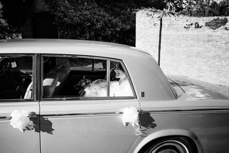 Bride smiling through the car window