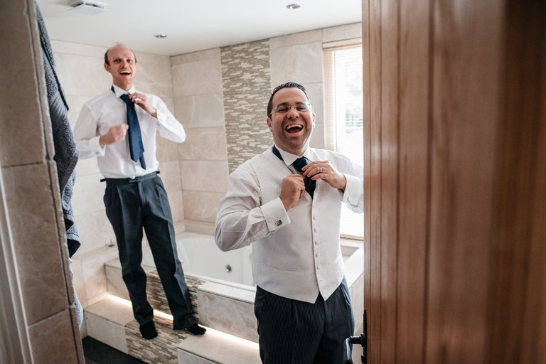 Pair of groomsmen laughing in the bathroom fixing their ties