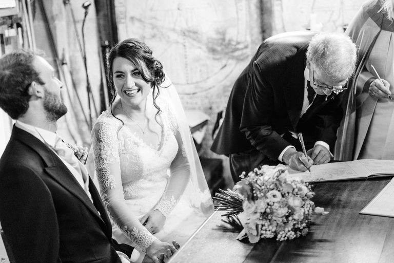 Bride smiling at her husband as witness signs the register