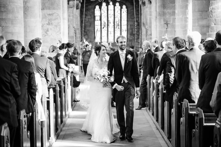 Walking down the aisle together at Melbourne Church in Derbyshire