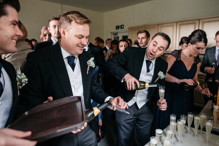 Groomsmen pouring champagne for guests