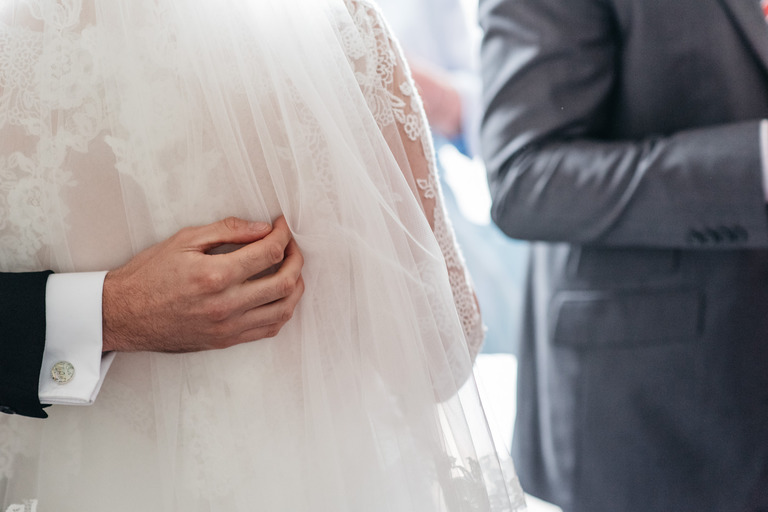 Groom's hand on his wife's dress