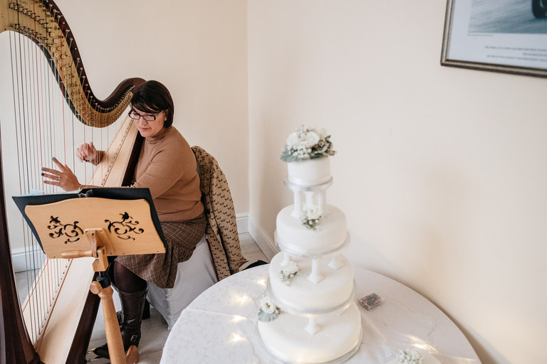 Harpist playing next to the wedding cake