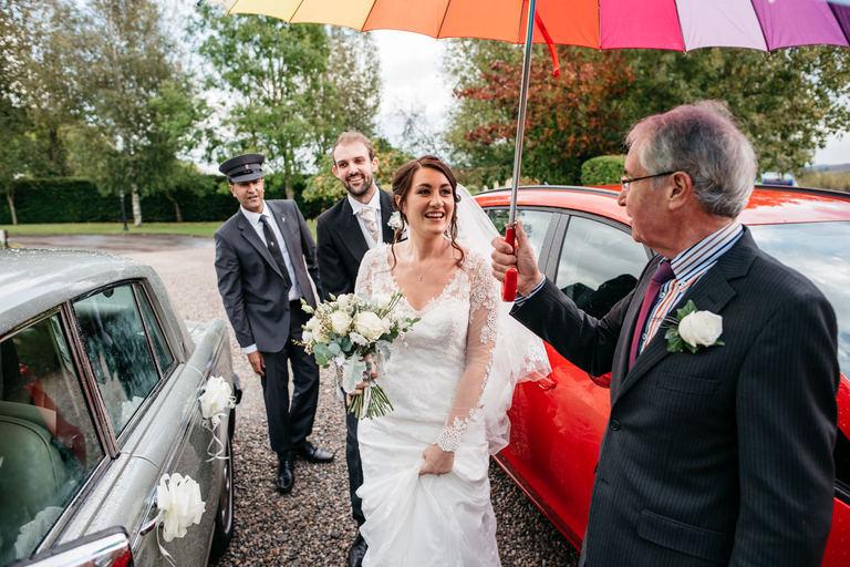 Bride and groom arrive at reception under umbrella