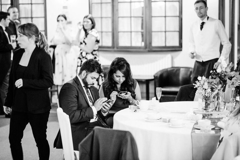 A couple of wedding guests checking their phones