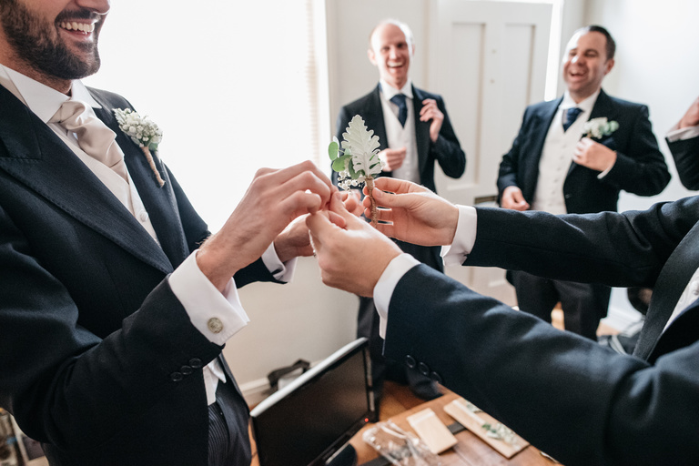 Groomsmen helping out with button hole