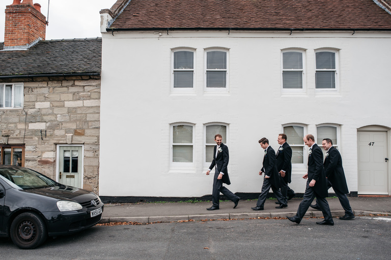 Groom and groomsmen walking to the church