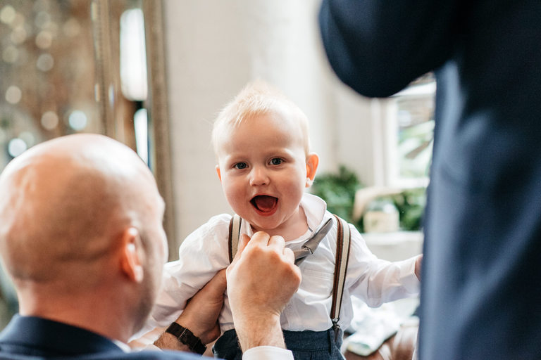 Groom helps his young son with bow tie