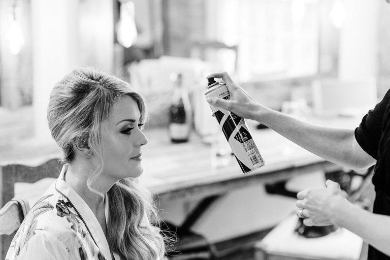 hair stylist applies hairspray