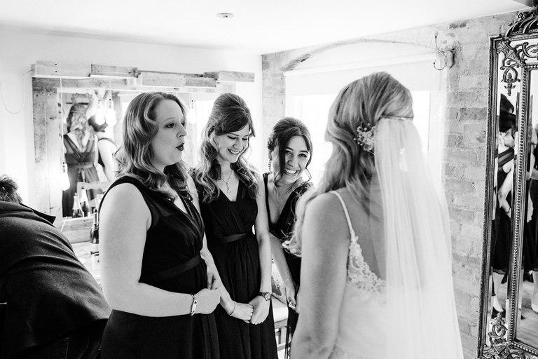 smiling bridesmaids admire bride in dress