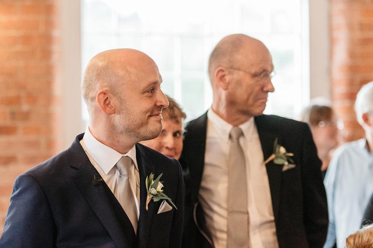 groom smiles as he sees bride walking down the aisle