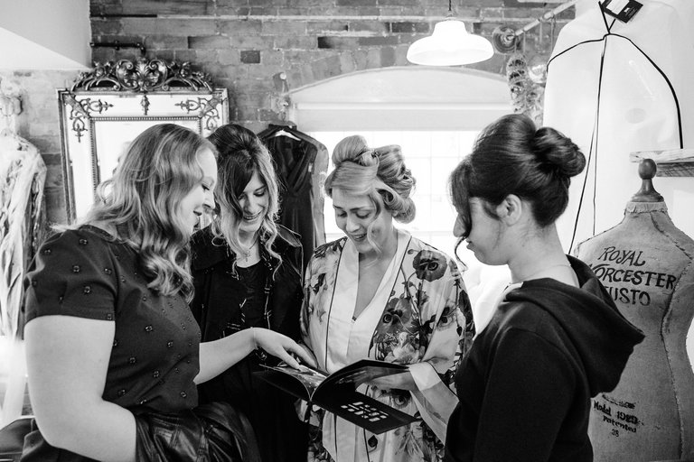 bride showing bridesmaids photo album