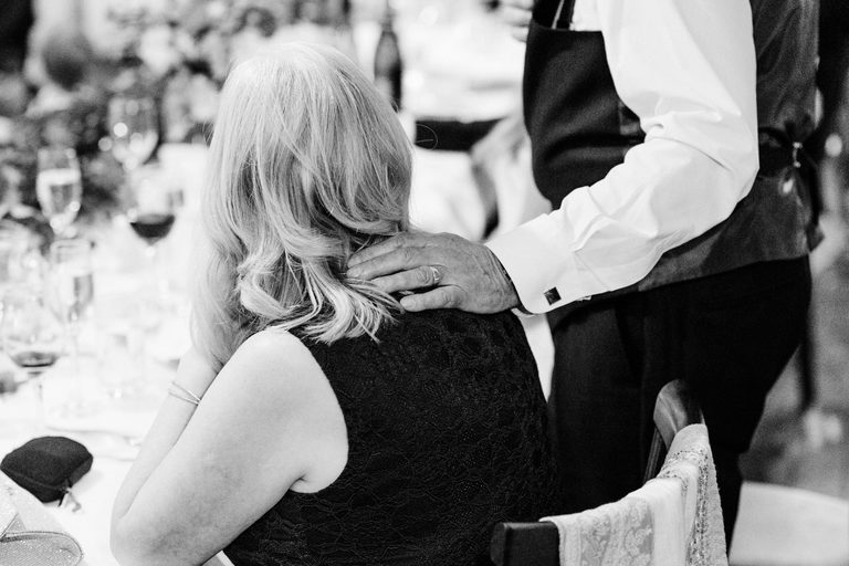 bride's father lays a comforting hand on his wife's shoulder