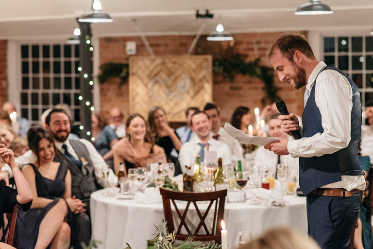 best man delivering his speech to laughing guests