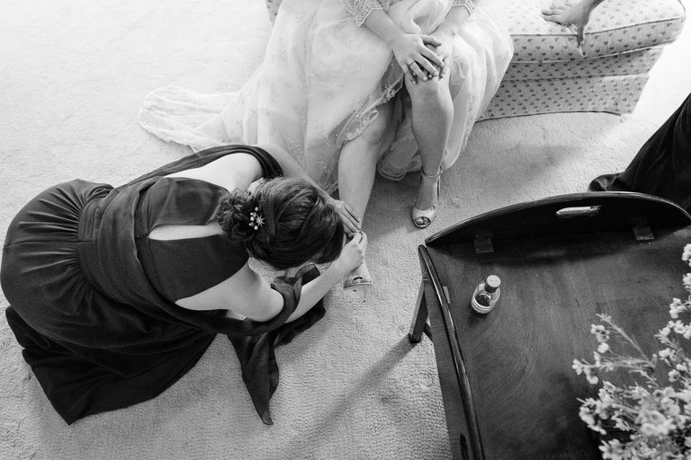 bridesmaid helping bride to put her shoes on