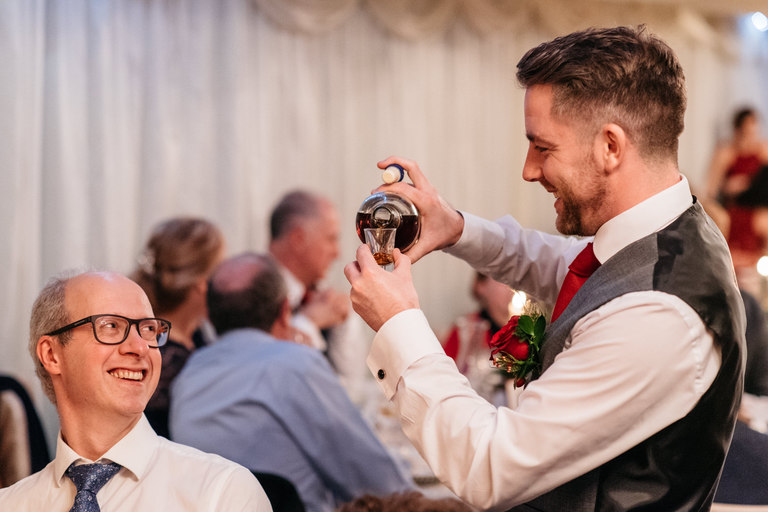 groomsman pouring rum for guests