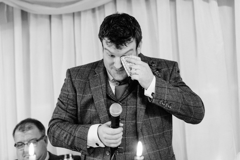 groom wiping his eyes during his speech