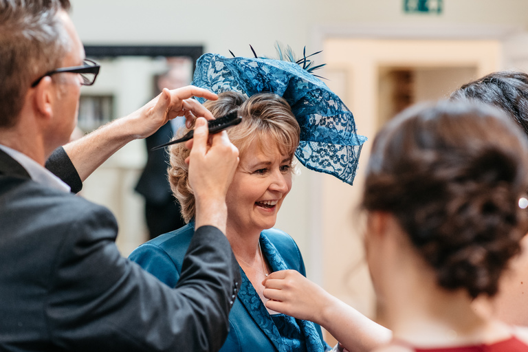 mother of the bride having her hat sorted