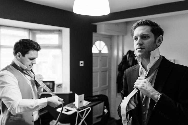 groomsmen tying their ties