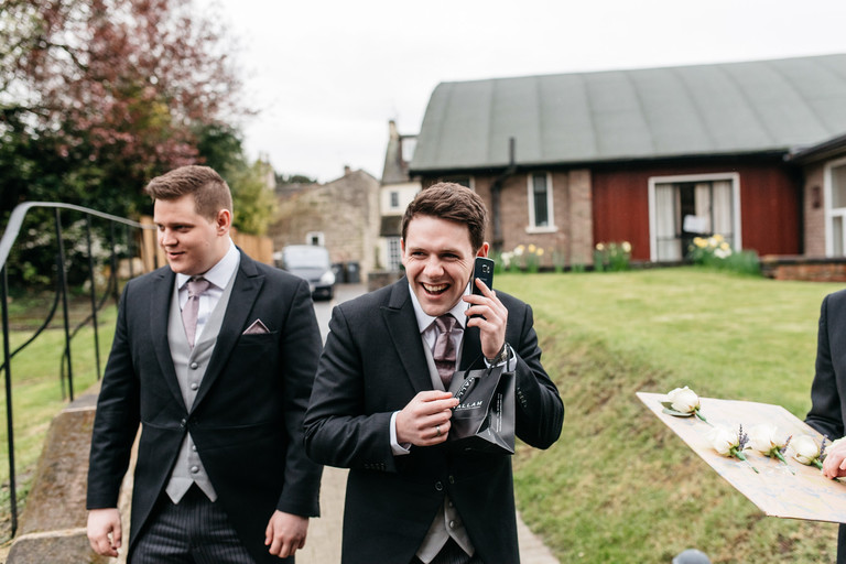 best man laughing on the phone