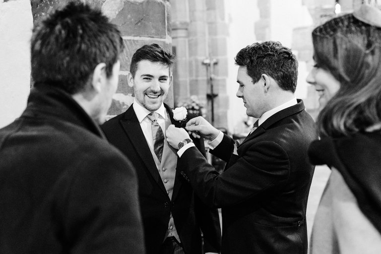 groomsman having his button hole fitted