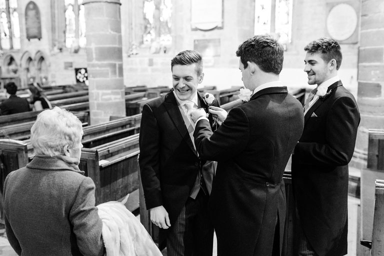 groom smiling at church assistant
