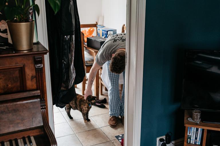 groom stroking his cat