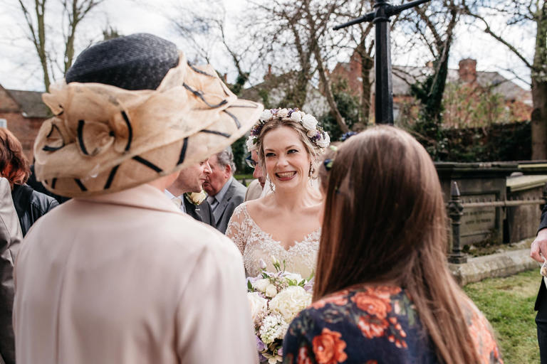 bride smiling with guests outside the church