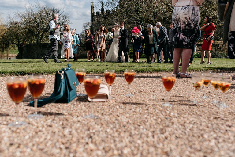 glasses of pimms on the ground while waiting for group shot
