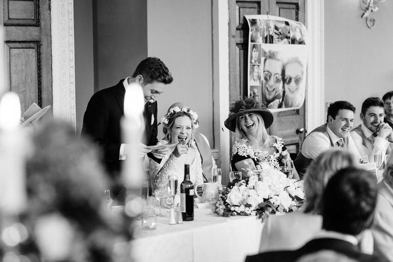 bride laughing during her husband's speech