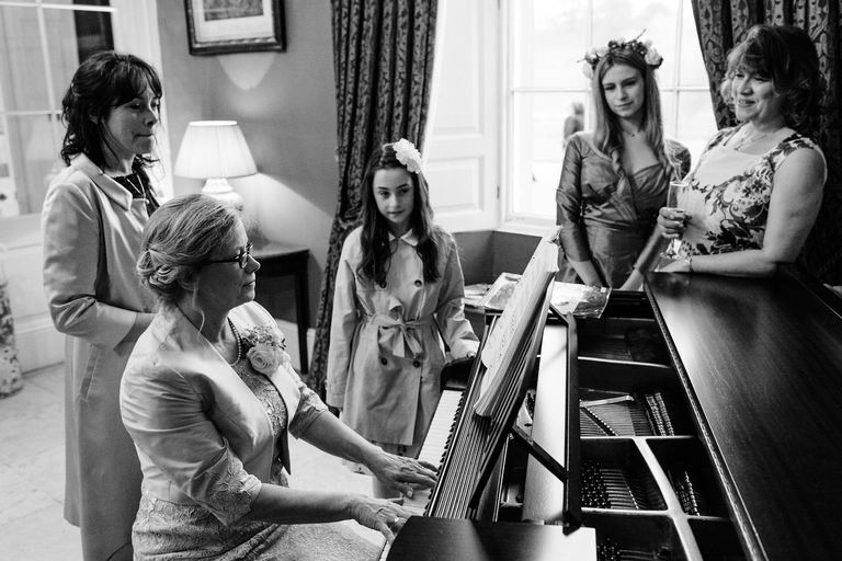 lady playing the piano for wedding guests