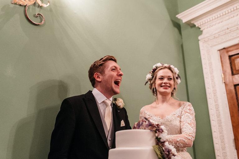 groom laughing during cake cutting