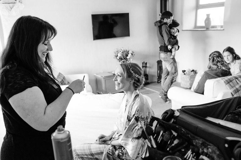 bride laughing with make-up artist