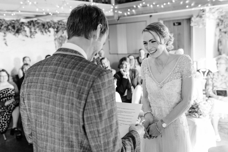 bride's face while groom reads vows