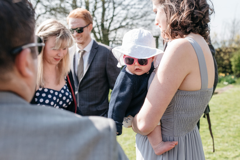 baby wedding guest in sun hat and sunglasses
