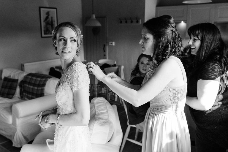 bridesmaid helping bride with her dress