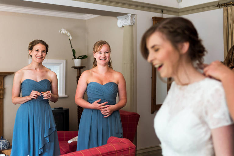 bridesmaids watching bride get into her dress