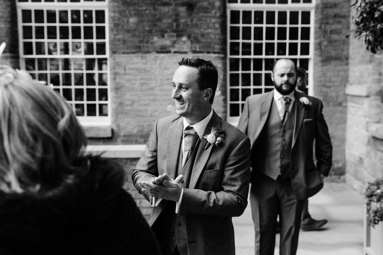 happy groom greeting guests