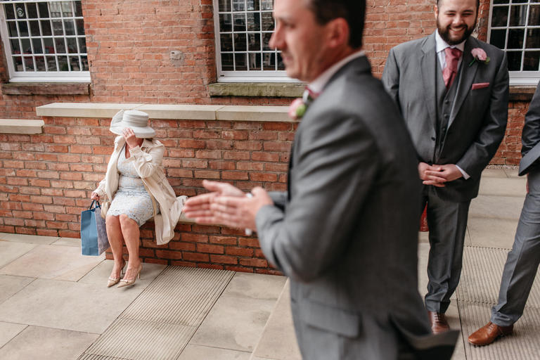 wedding guest holds onto her hat