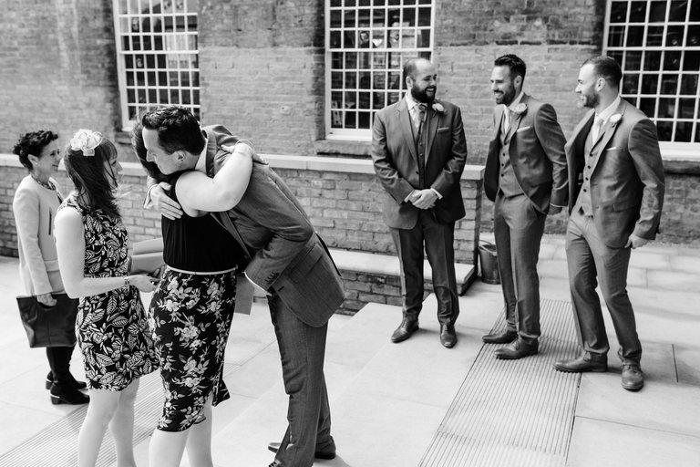 groom and groomsmen greet guests