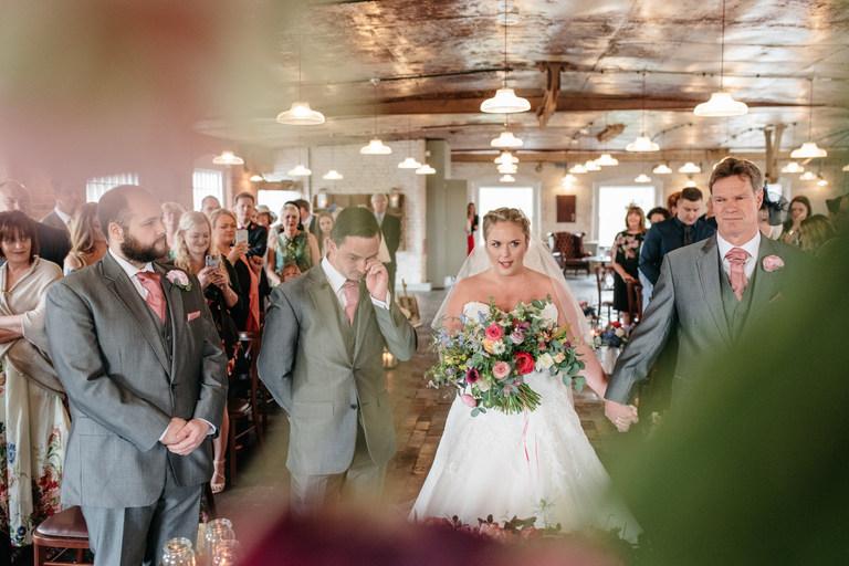bride walks down the aisle groom wiping eyes