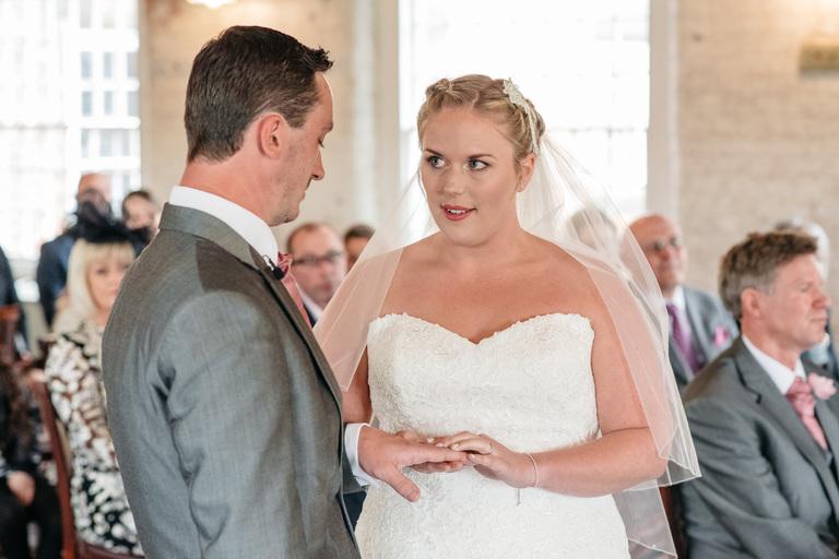 bride putting ring on her husband's finger