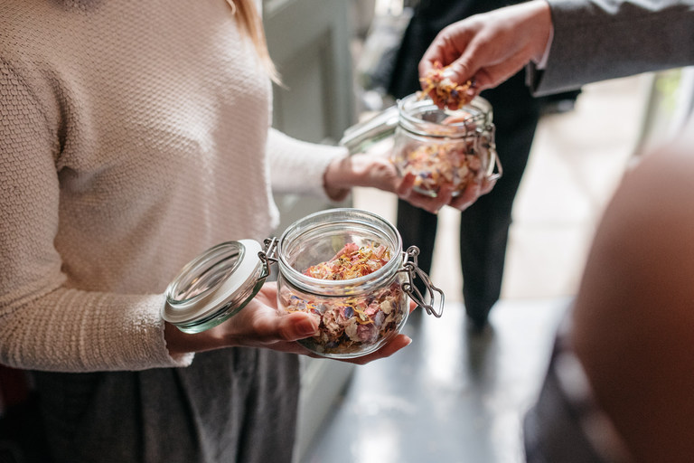 guests grabbing petal confetti from a jar
