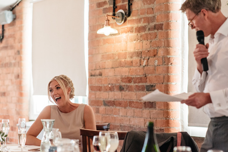 bridesmaid laughing at her dad's speech