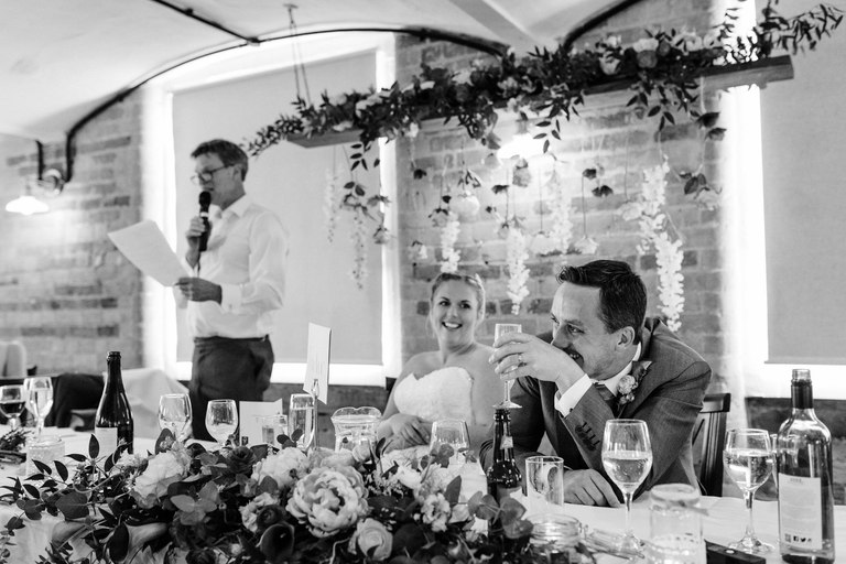 groom laughing at bride's father's speech