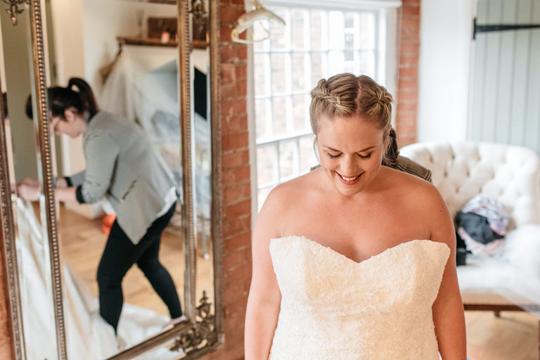 bride smiling getting into her dress