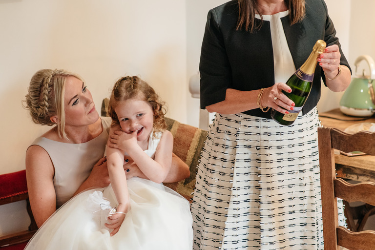 happy flower girl and mum opening champagne